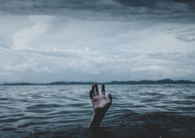 PTSD hand in ocean reaching above water