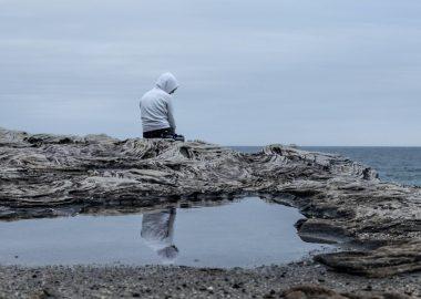 sitting by self in hoodie on rocks